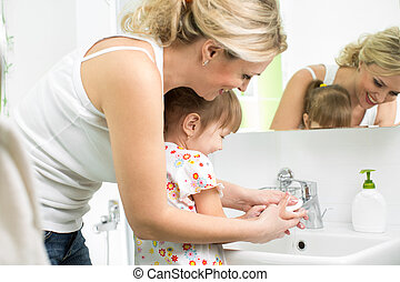 mother washing baby hands