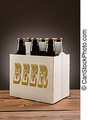 Six Pack Beer on Wood Table - Closeup of a six pack of brown...