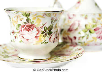 teacup on saucer against sugar bowl decorated with roses...
