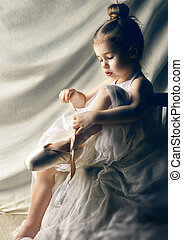 dancing gracefully - Little girl trying on ballet shoes