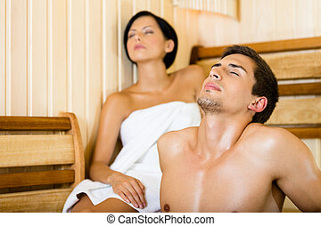 Half-naked man and female relaxing in sauna Concept of...