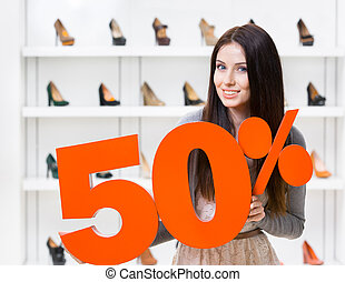 Woman keeps the model of 50% sale on pumps standing at the...