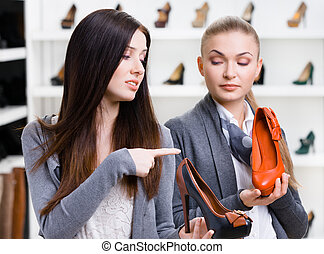 Shop assistant offers stylish shoes for the customer - Shop...