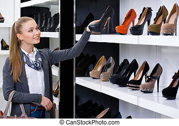 Woman looking at the rows of shoes