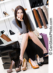 Woman trying on footwear in the shop - Woman sitting on the...