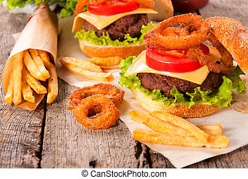 Junk food - Onion rings,french fries and cheeseburger on the...