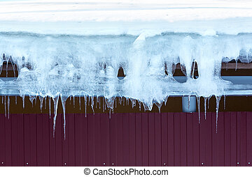 Icicles and snow on a roof - Snow and icicles hanging from...