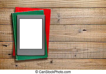 Ereader and old books on wooden background