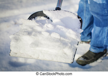 Man with a snow shovel in the hands