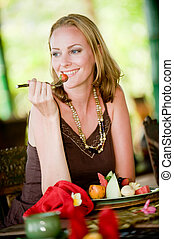 Woman Eating Breakfast - An attractive woman eating a...