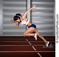 sprinter woman - Woman sprinter leaps from starting block