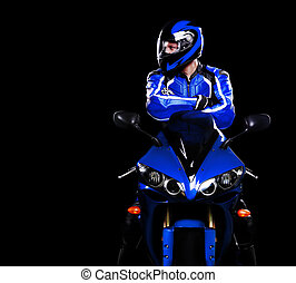 Motorcyclist in dark blue equipment looking to the copy...