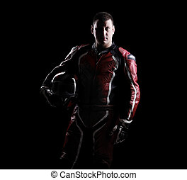 Low key silhouette of a biker holding helmet on black...