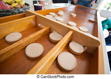 A traditional Dutch game called 'sjoelen'. The wooden disks...