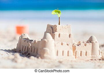 Sand castle and beach toys at tropical coast