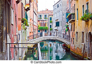 Venetian canal - A canal and old white bridge in Venice,...