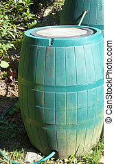 Connected Rain Barrels - Two green plastic rain barrels are...