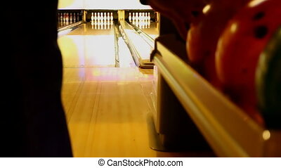Ten pin bowling ball strike - Man picks an orange bowling...