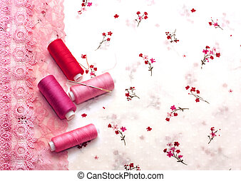 pink spools of thread on a floral fabric