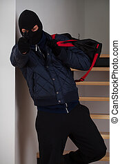 Aiming robber with bag - A masked robber with bag aiming at...