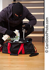 Stolen goodies bag - A thief searching a bag with stolen...
