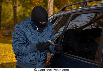 Masked car criminal - A masked criminal about to steal a car