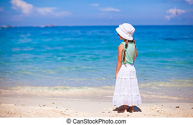 Little sweet girl on a tropical beach with turquoise water