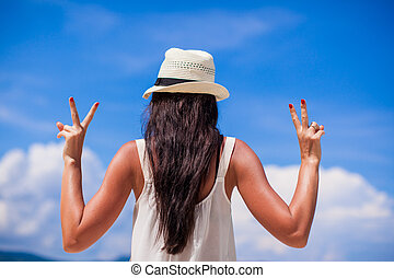 Young woman with raised hands at perfect beach