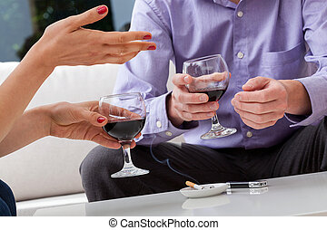 Smoking on a date - Man and woman smoking and drinking wine...