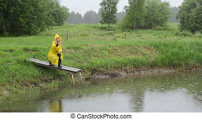 farmer feed fish rain - Farmer woman girl with waterproof...