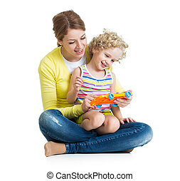 Mother and kid girl having fun with musical toy. Isolated on white background