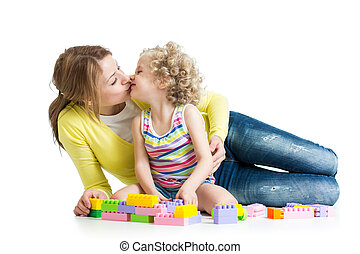 cheerful mother and kid play with toys on floor