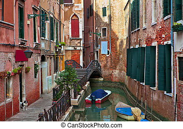Typical venetian canal among old building - Boats on narrow...