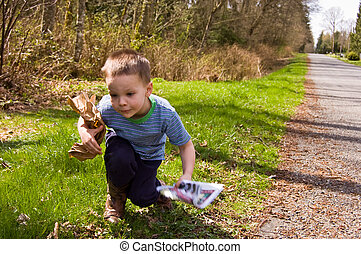 Young Boy Picking up Trash on Roadside - A young 4 year old...