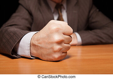 My word is law Close-up of man in formalwear holding fist on...