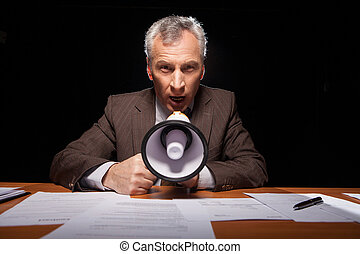 Listen to me! Furious senior man in formalwear sitting at his working place and shouting at megaphone while isolated on black background