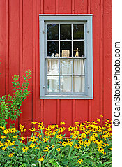 Window on old red building with flowers in front