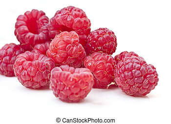Raspberries - a close-up of raw raspberries on a white...