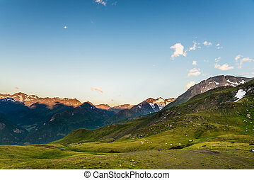 Early morning in the alps with sunlit mountain peaks and...