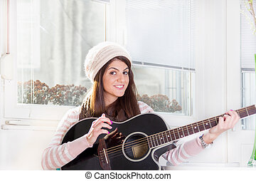pretty girl playing the guitar and smiling