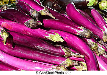 Purple Asian Eggplants at Farmer's Market - a pile of bright...