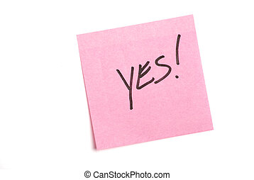 "Pink post it note isolated on white with ""yes\"" written."