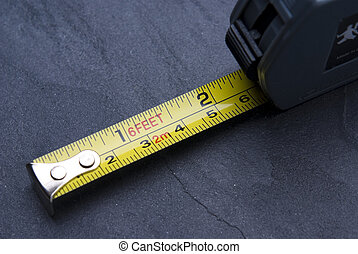 Tape measure with imperial and metric markings on slate...