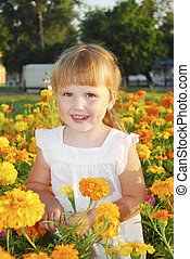 Summer girl stands in the colors of Marigolds