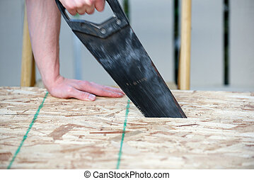 Side view of a man using a hand saw with motion blur