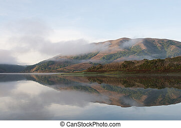Hills reflected in surface of lake on a foggy morning