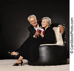 Senior couple celebrating holiday - Senior couple sitting in...