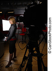 full length news reporter in television studio before...