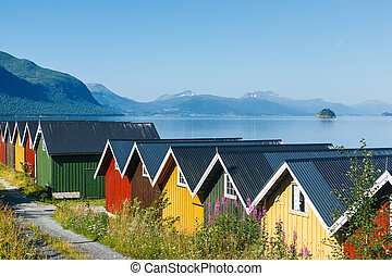 Colorful camping cabins on the fjord shore