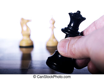 Black queen moved on chessboard - Chess piece moved by hand...